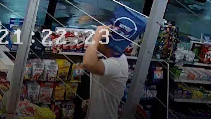 Robber hides face with bag - then removes it to carry money