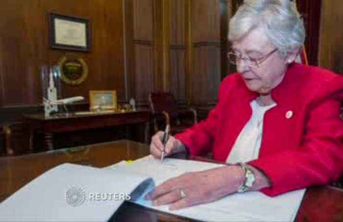 Alabama governor signs strict abortion ban into law