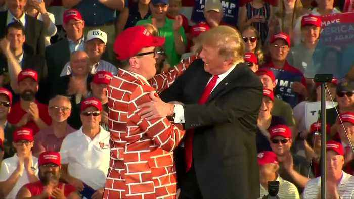 Trump invites man in wall-suit up on stage