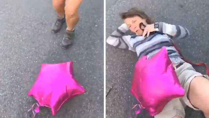 DIDN'T SEE THAT COMING: WOMAN JUMPS ON BALLOON ONLY TO FALL OVER BACKWARDS AND CRACK HER GLASSES