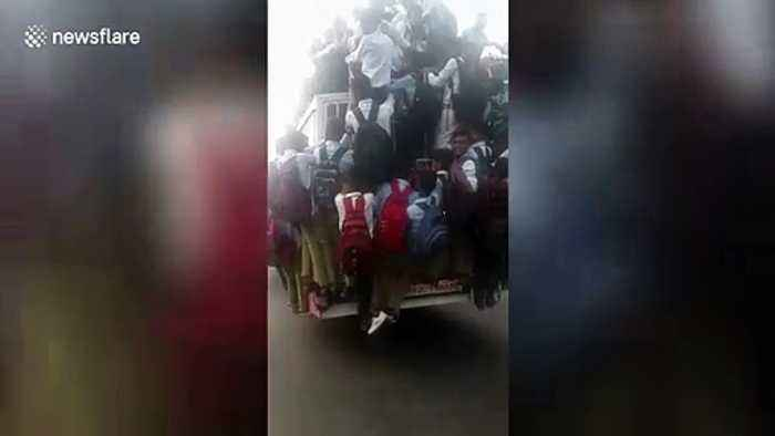 School students cling precariously to moving bus in northern India