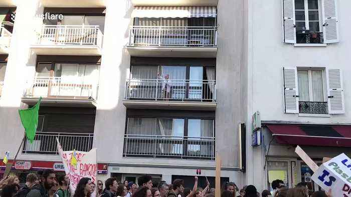 Elderly woman blows kisses to climate strikers marching below her balcony