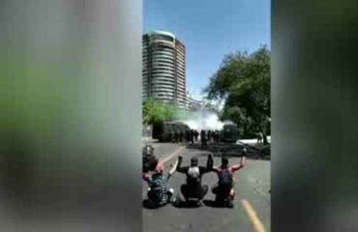 Protesters with hands up shot by police in Chile