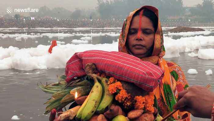 Hindus perform religious ceremony in sacred river covered in toxic foam