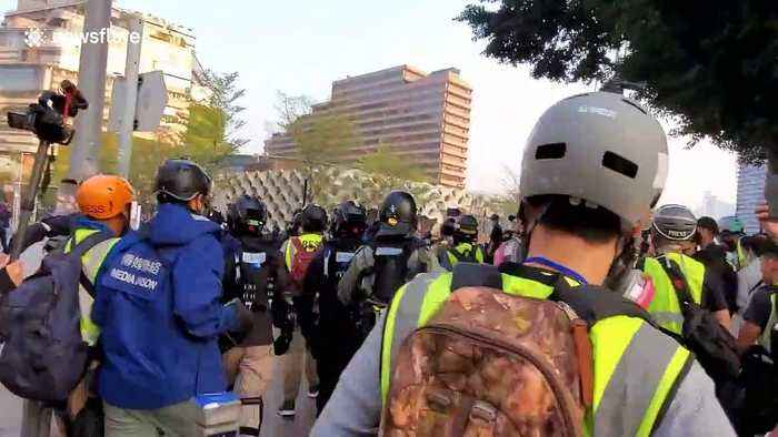 Riot police charge protesters and throw tear gas during legal Hong Kong march