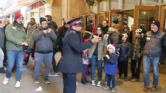 Salvation Army officer dancers with passerby in New York