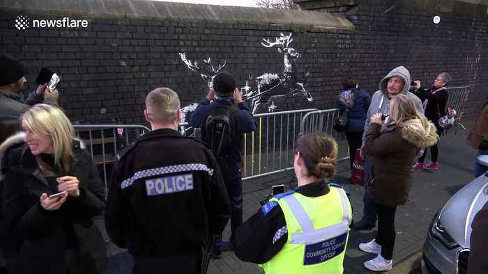 Police pose for pictures as they guard new Banksy artwork in Birmingham highlighting homelessness at Christmas