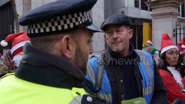Police officer confronts Extinction Rebellion activists leaving coal outside Tory HQ in London