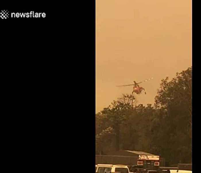 Water-dropping helicopter waters down NSW fires as it continues to grow near Batemans Bay evacuation center