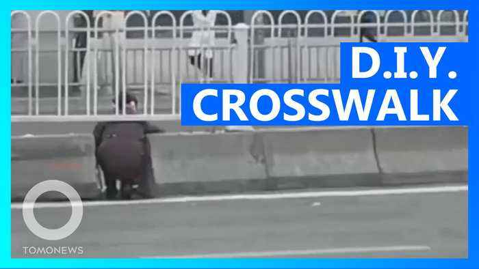 Chinese jaywalkers cross six-lane road by squeezing through crack