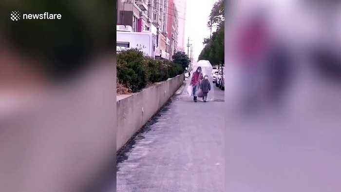 Chinese mother and daughter walk on street covered in huge plastic bag amid coronavirus outbreak