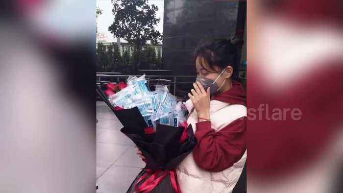 Chinese girl receives bunch of flowers packed with masks and ethyl on Valentine's Day during coronavirus outbreak