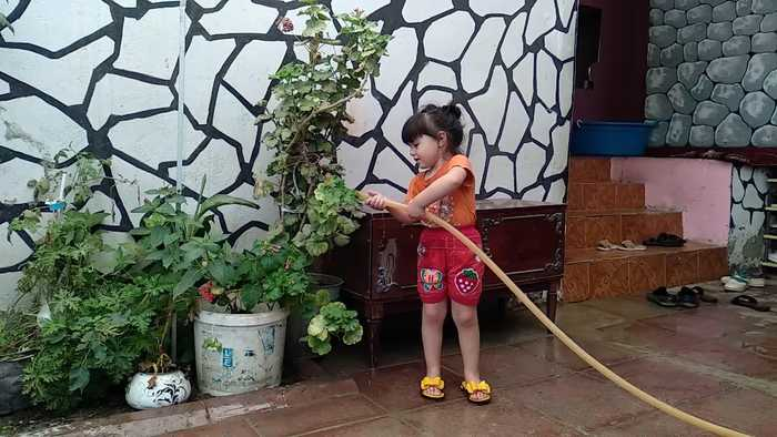 Water Gushes From Hose and Sprays Little Girl as She Waters Plants