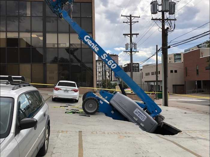 Boom lift falls through underground parking garage in Denver; 2 workers rescued