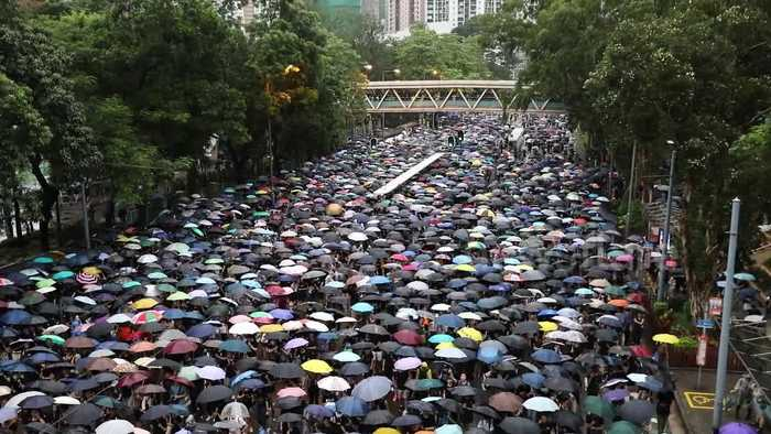 Protesters shout 'Hong Kong People, go for it!' as they march through rain-soaked streets