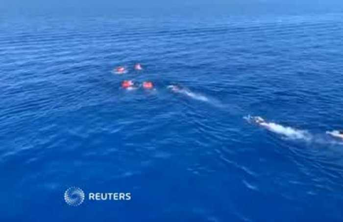 Stranded migrants try to swim to Italy