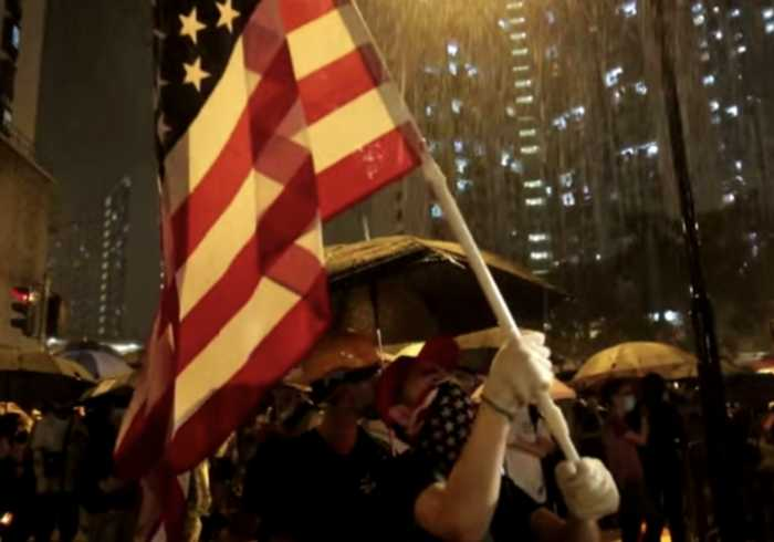 Protester Waves American Flag, Sings 'The Star-Spangled Banner' at Rainy Police Station Demonstration