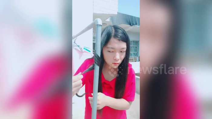 Chinese girl uses a hot outdoor water pipe to curl her hair