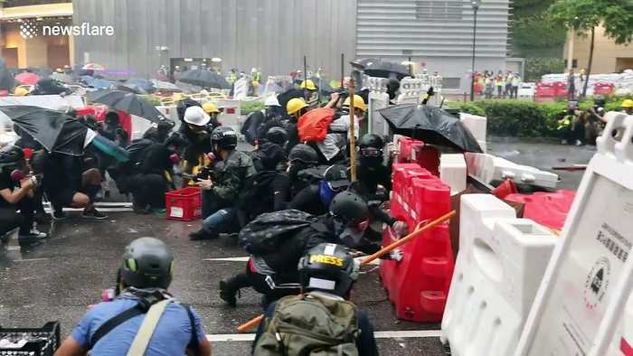 Hong Kong protesters take cover behind barricades as police fire tear gas
