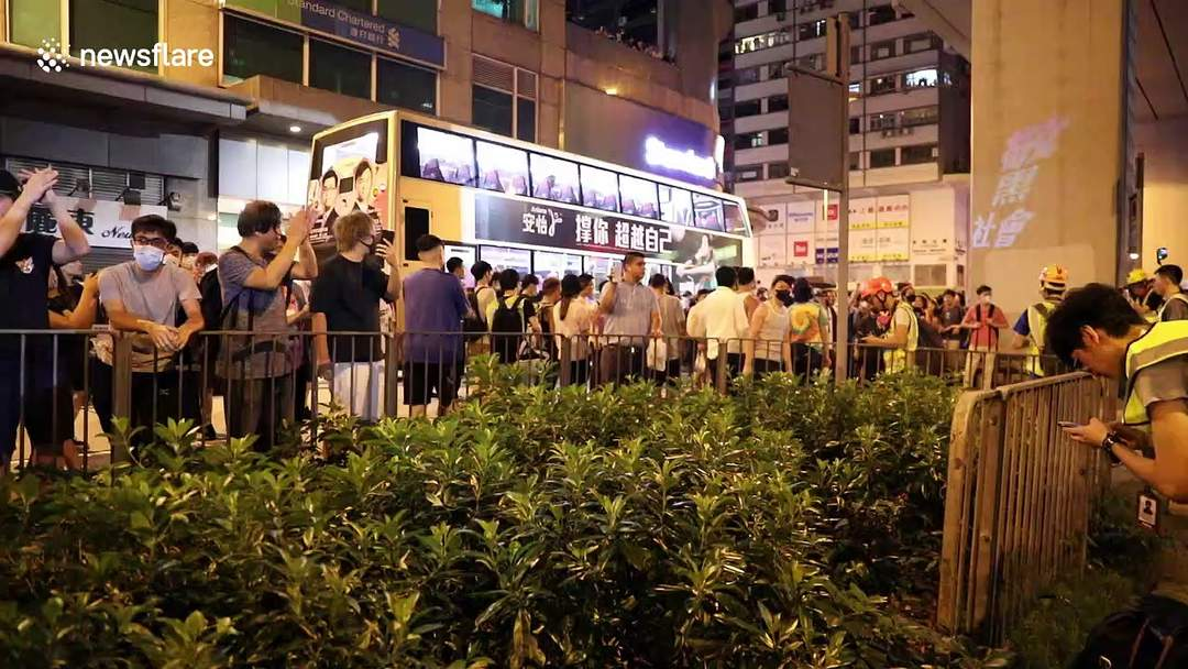 Hong Kong police take cover behind netting and riot shields