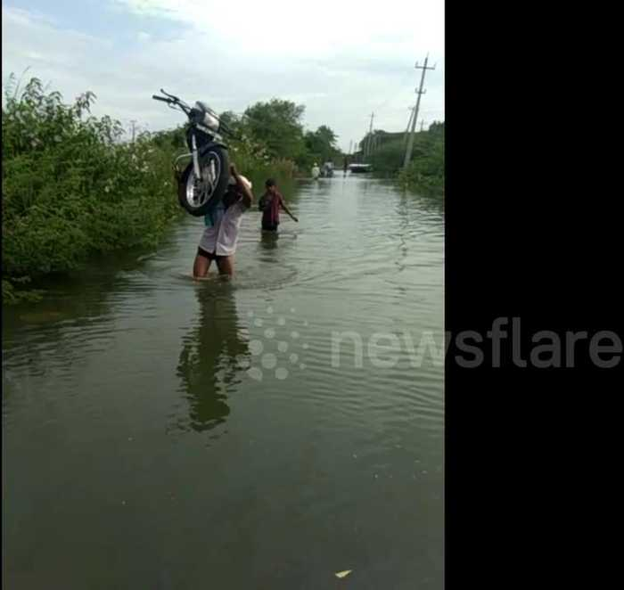 Indian man carries motorbike on shoulder over flooded road so it doesn't get wet