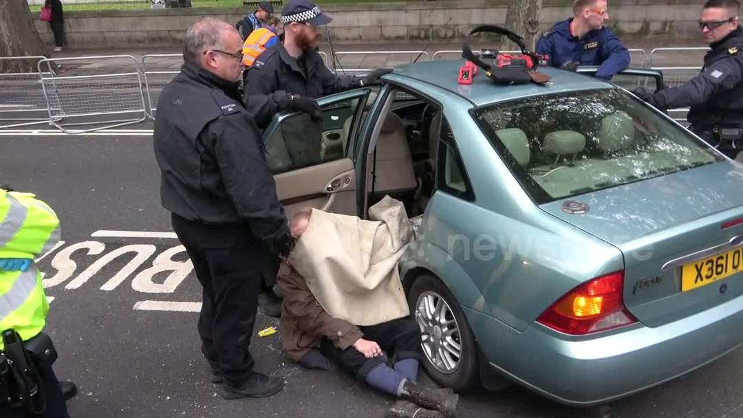 Police remove Extinction Rebellion protesters chained to car outside Ministry of Defence in London