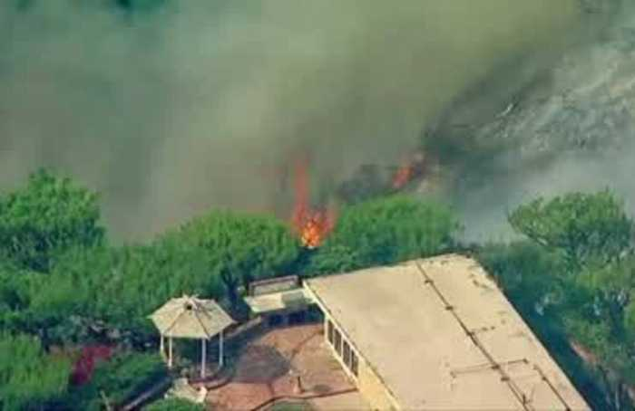 Wildfire threatens homes in wealthy California neighborhood