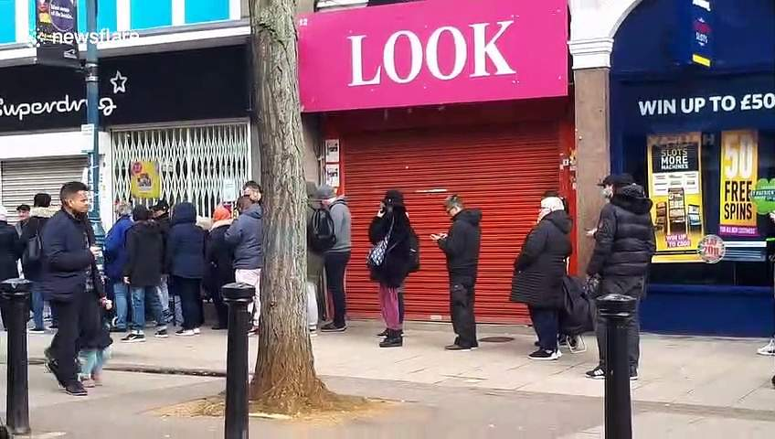 Customers queue outside London Superdrug for hand santiser