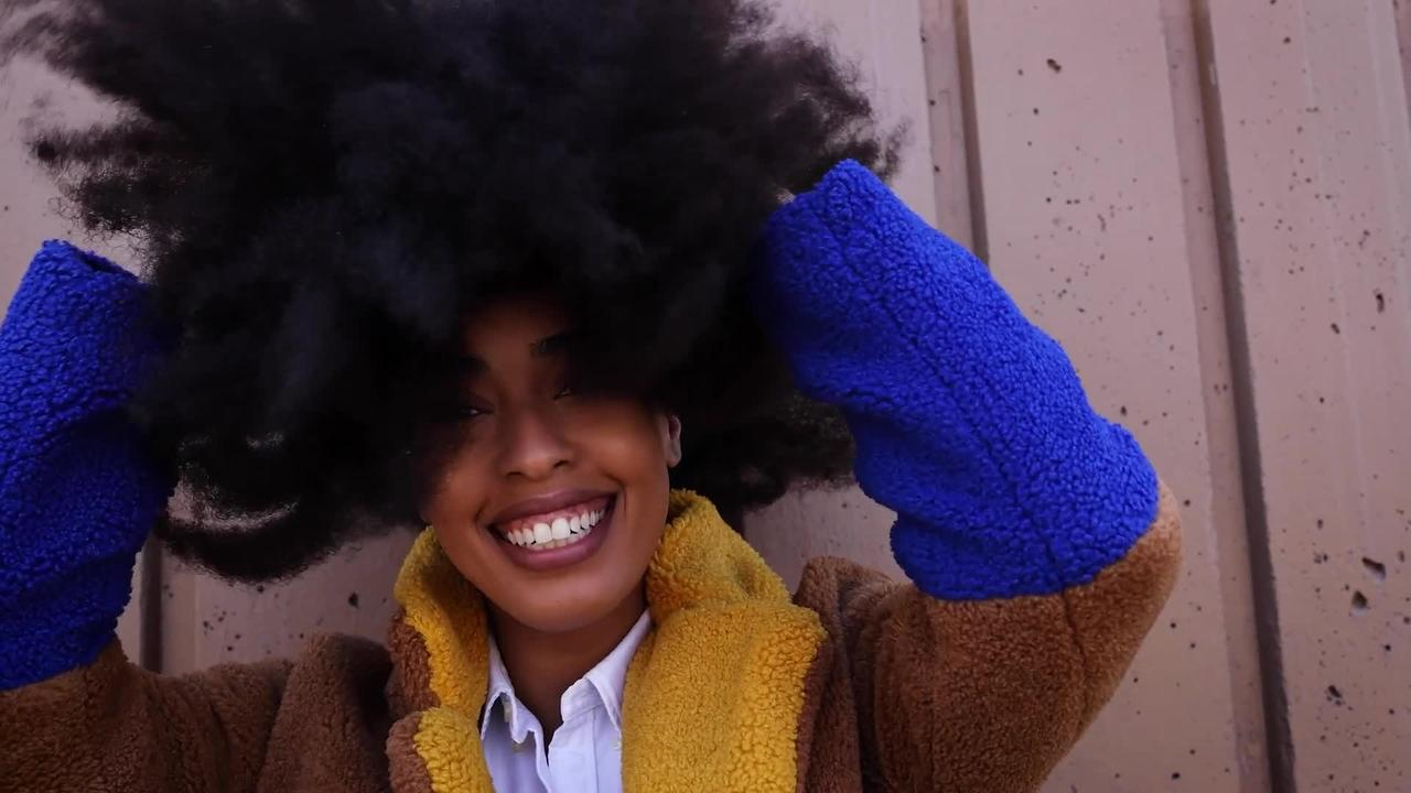 A woman who stopped having her hair straightened to save money has grown one of the world's largest AFROS - which stands at a wh