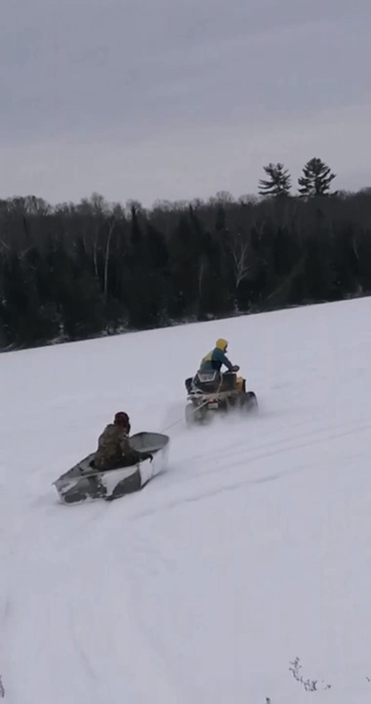 Person Riding ATV on Snow Pulls Another Person in Boat