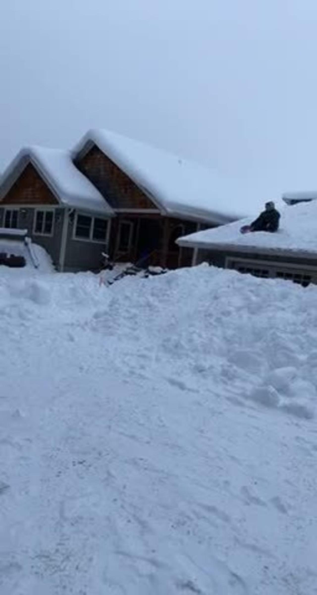 Man Sleds Down Sloped Roof of the House and Faceplants to the Snowy Ground