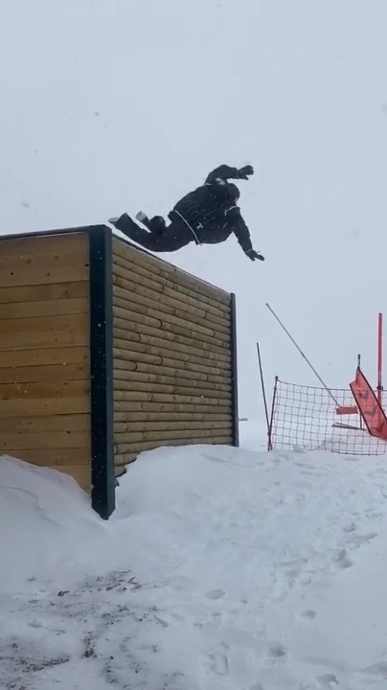 Guy Trying to Snowboard Down Icy Platform Slips and Falls Down to the Snowy Ground