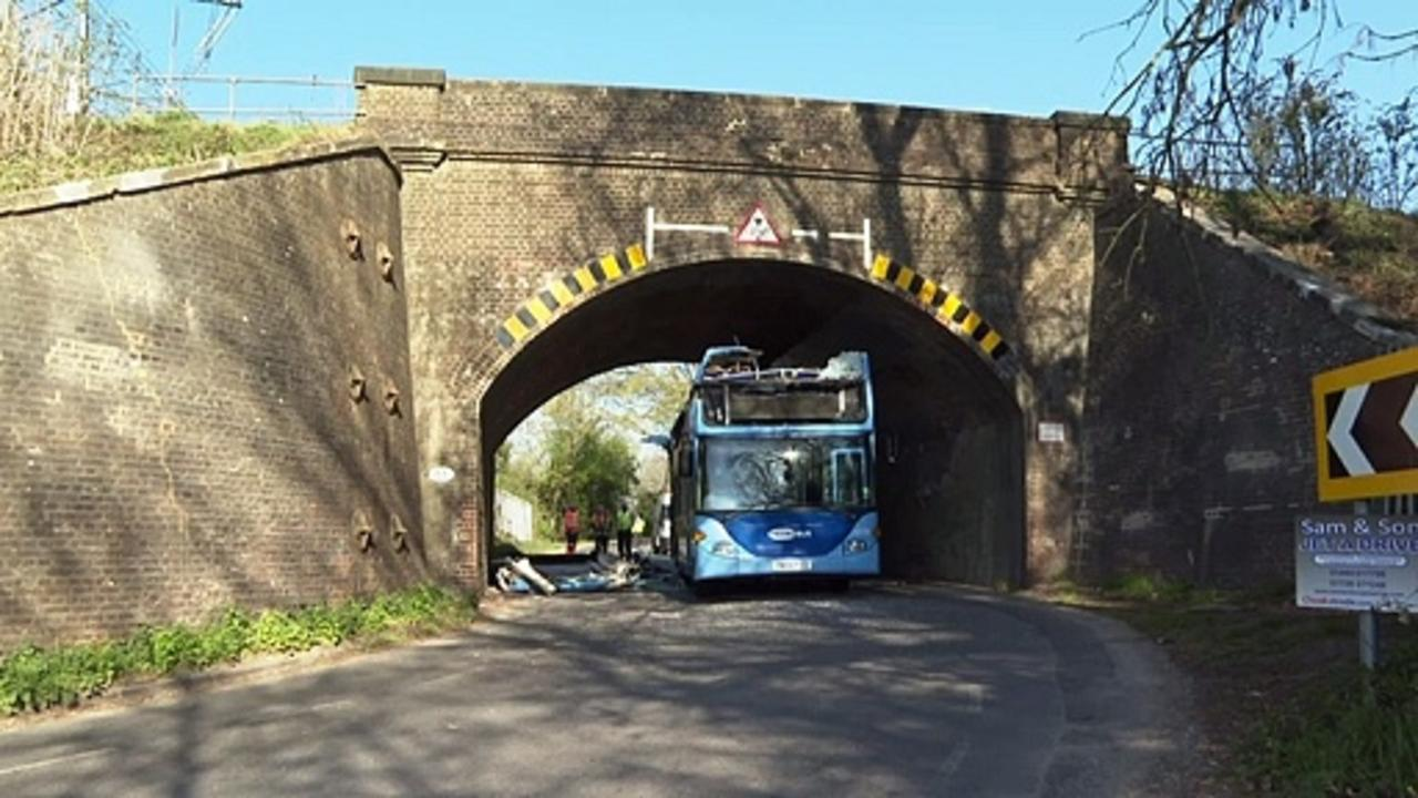 Double decker bus crashes into railway bridge