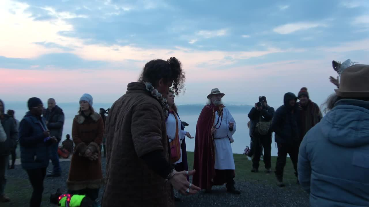 Pagans celebrate May Day and Beltane at the Glastonbury Tor as the sun rises above the horizon