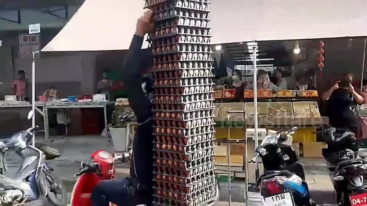 Delivery man carries 40 trays of EGGS on the back of his scooter