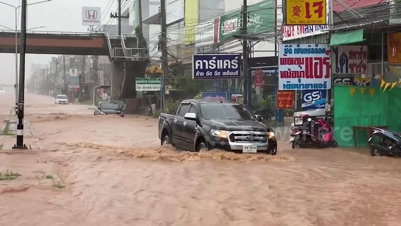 Cars drive through flooded roads after heavy rain in Thailand