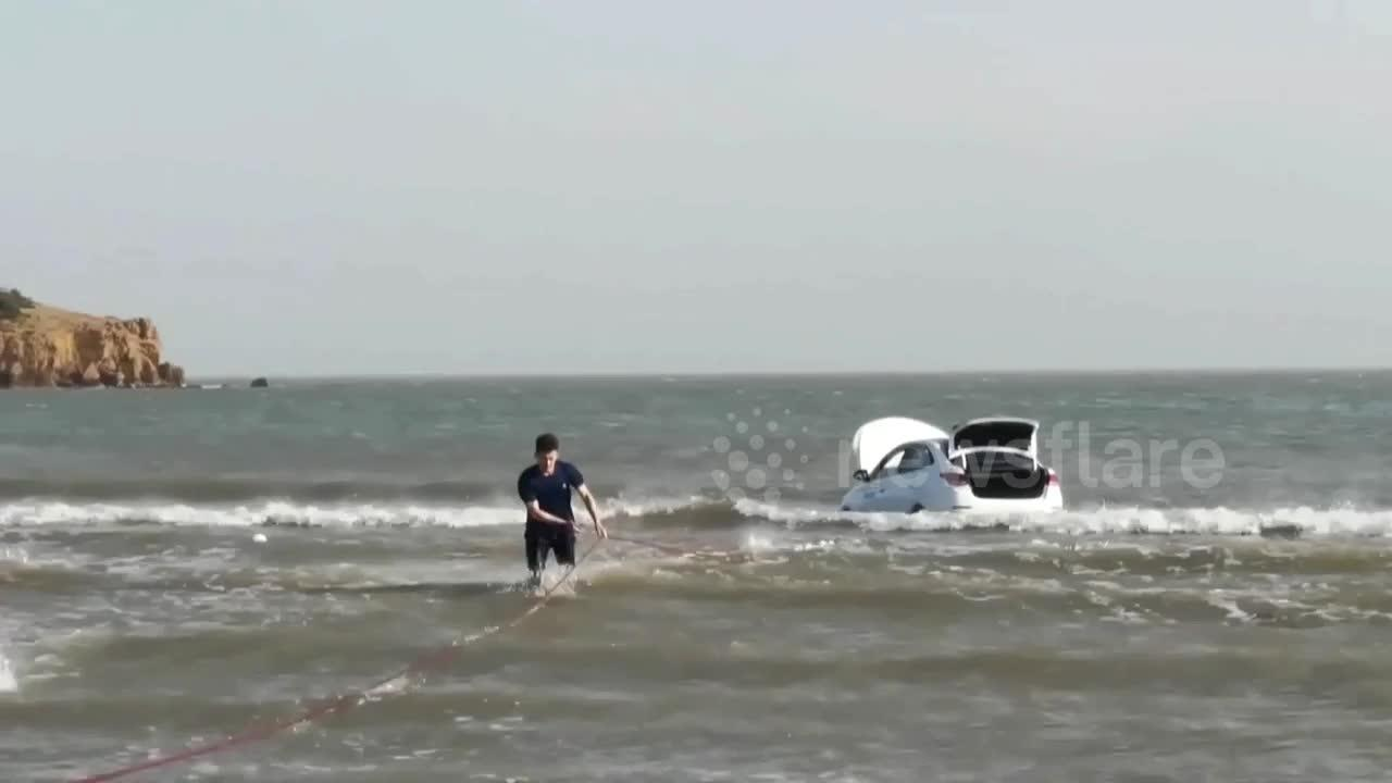 Chinese firefighters drag vehicle to shore after motorist parks on beach as tide rises