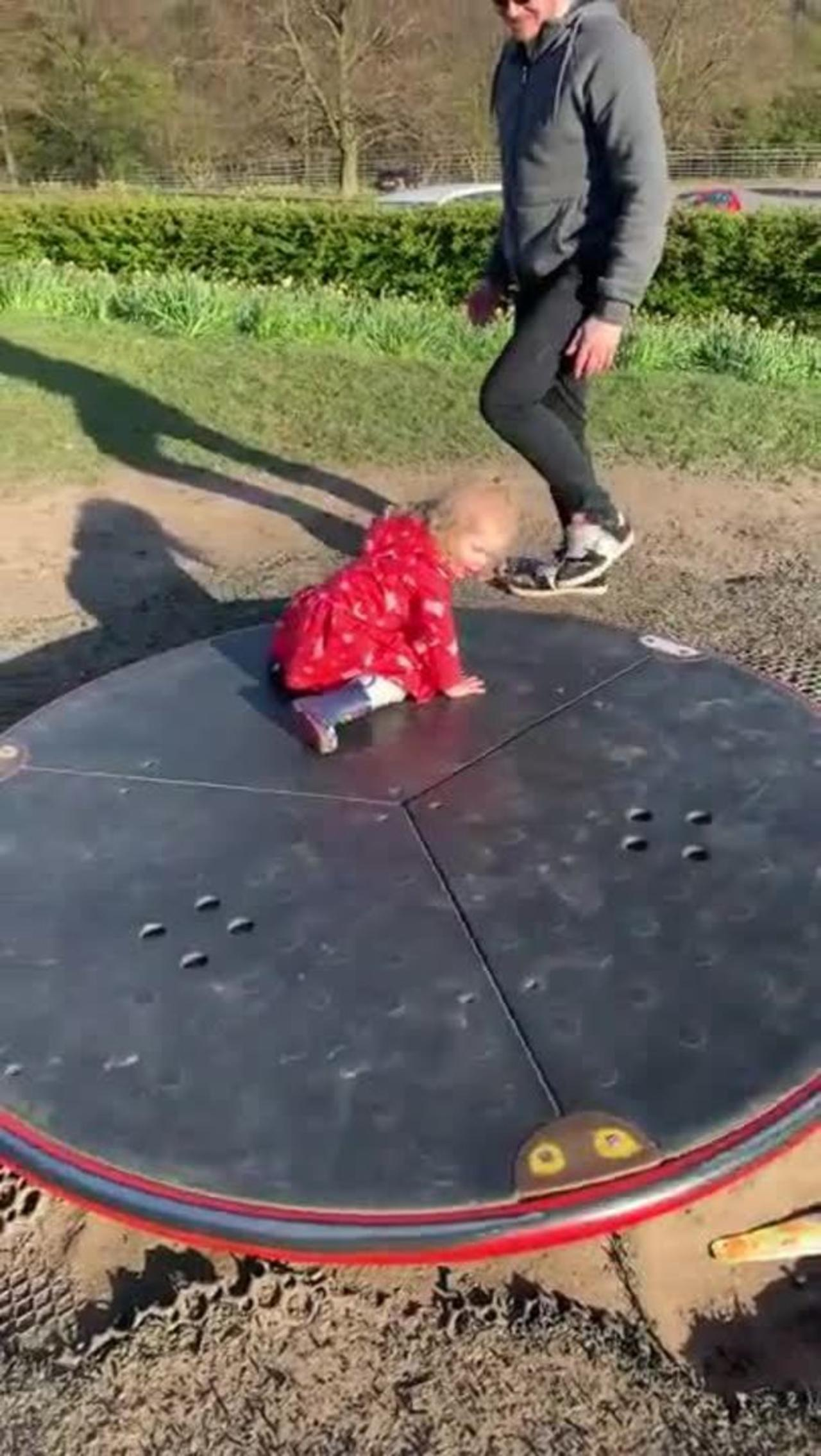 Father Saves Daughter From Falling Off Of Roundabout While Playing On It