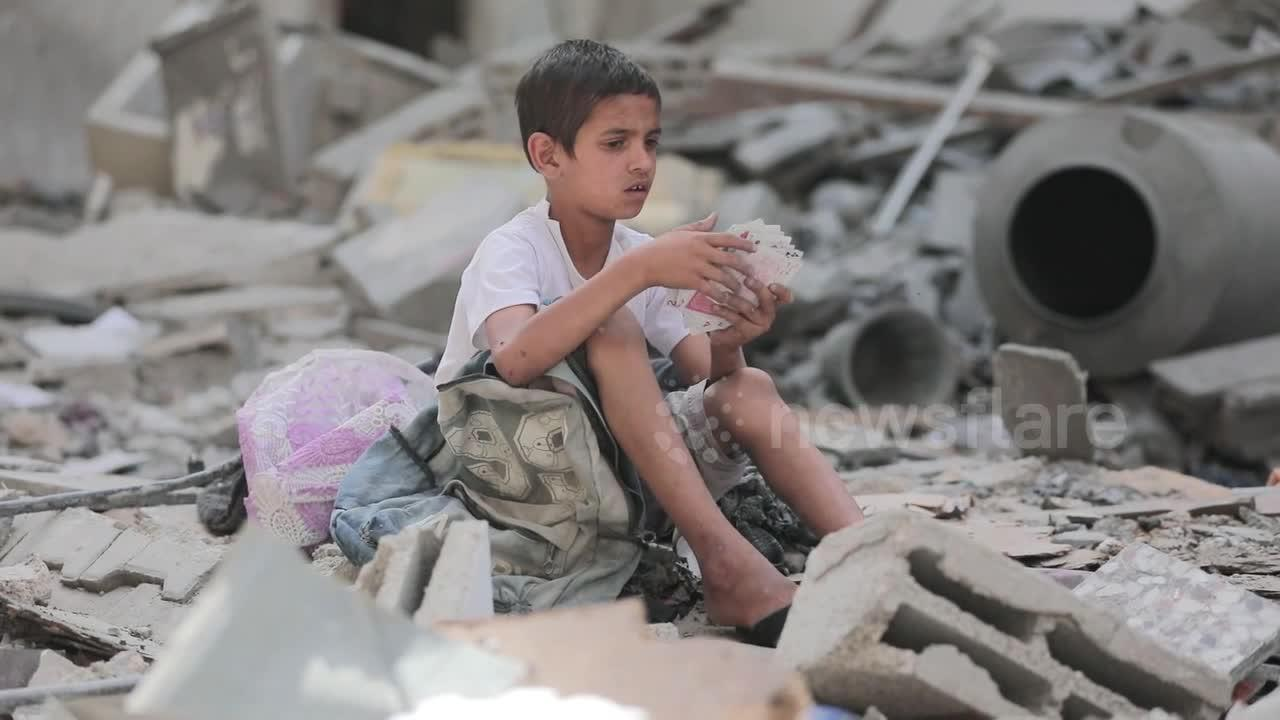 Palestinian boy picks out playing cards from rubble left by Israeli airstrikes