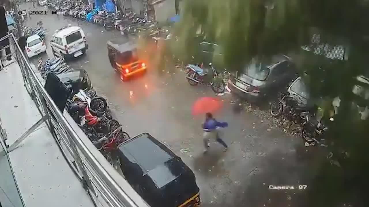 Woman dodges falling tree during cyclone Taukte in Mumbai, India