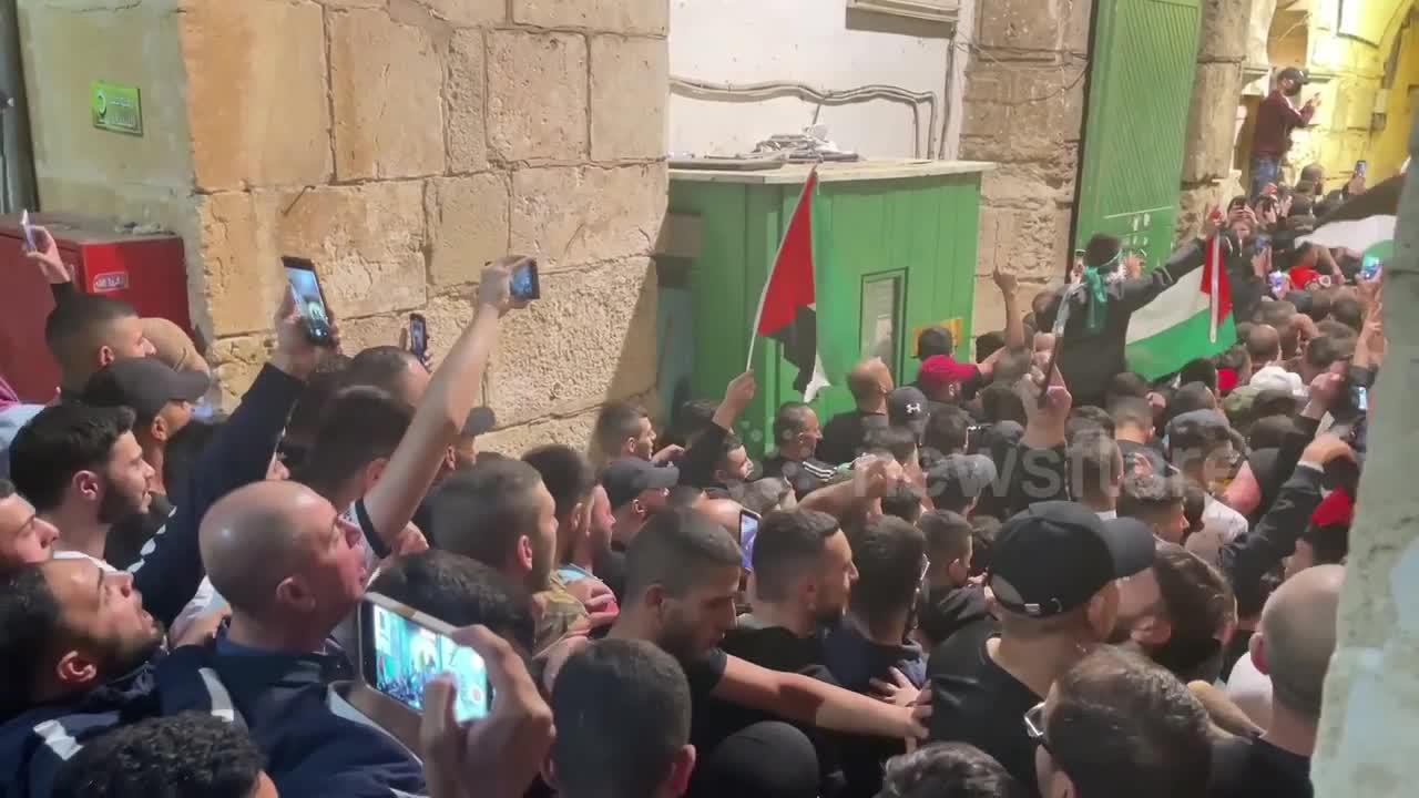 Palestinians celebrate in the streets following a ceasefire between Israel and Hamas