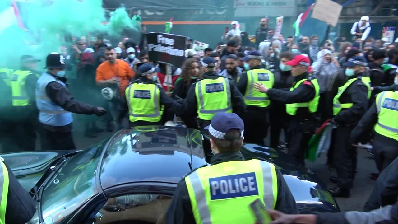Pro-Palestine protesters in London damage a car as police rush in to protect the vehicle