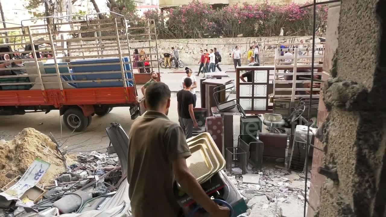 Palestinians collect their belongings from Al-Jawhara tower destroyed during Israeli airstrikes