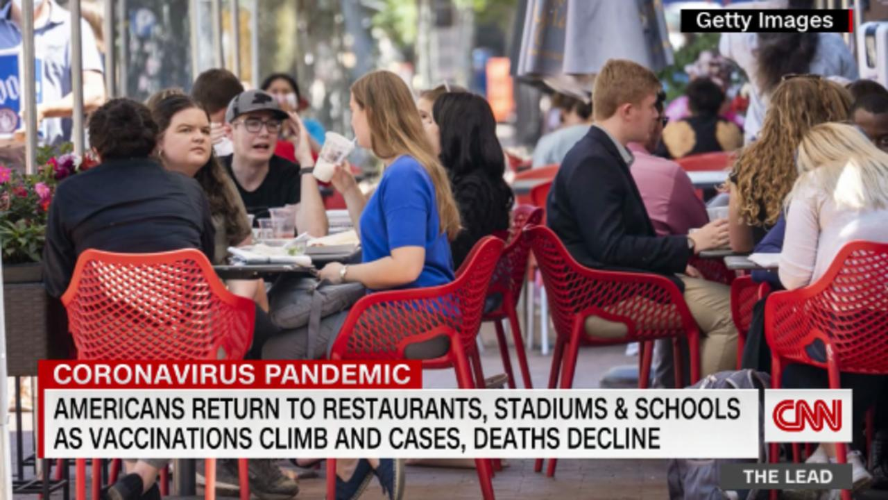 Americans return to restaurants, stadiums and schools, as vaccinations climb and cases, deaths decline