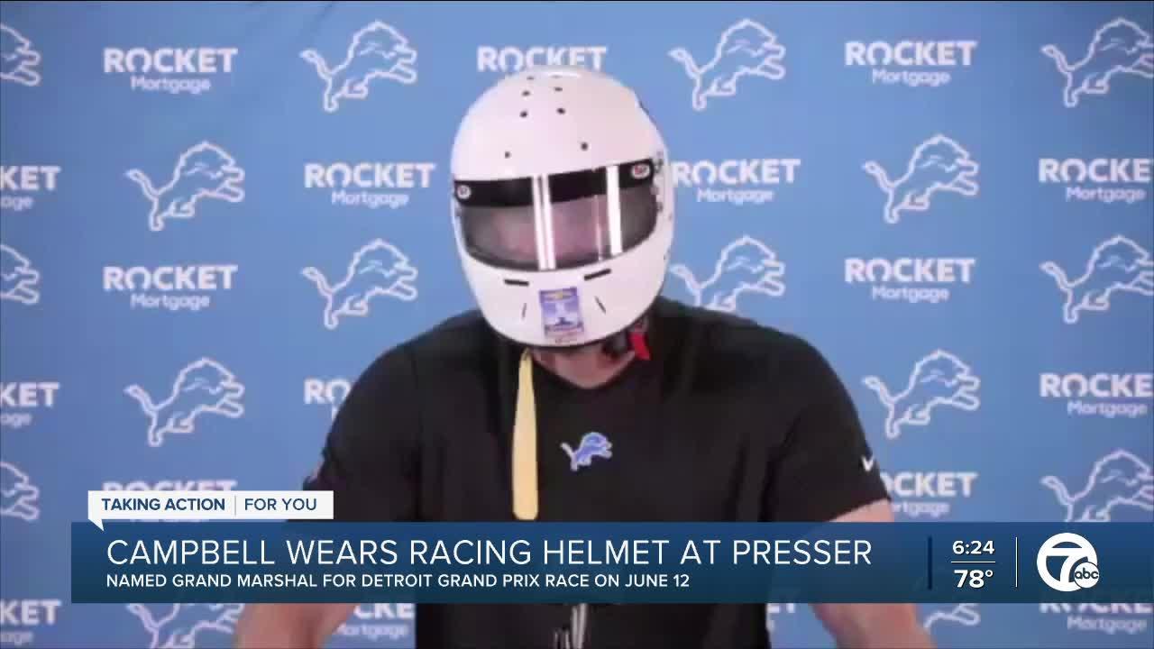 Dan Campbell wears racing helmet at press conference