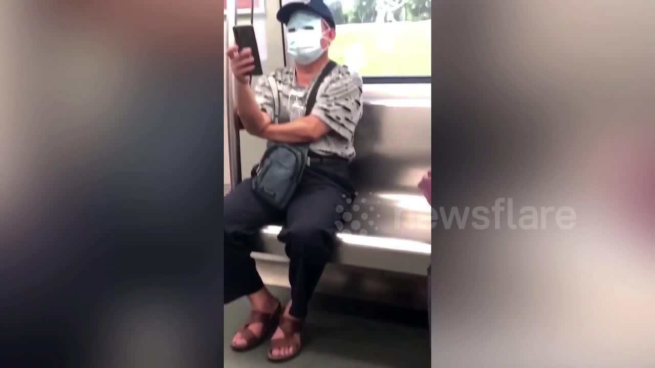 Chinese man uses masks to cover his whole face on train