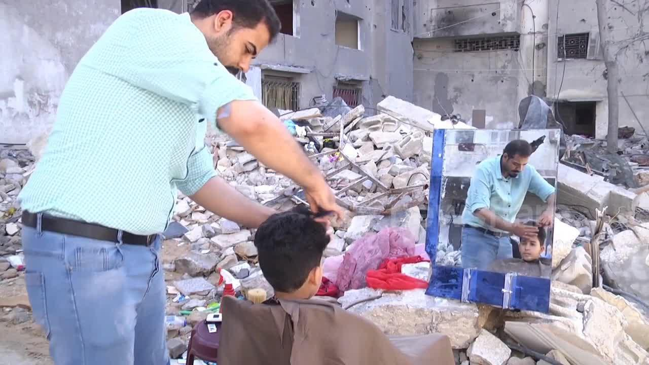 Palestinian barber sets up hair salon on ruins of his old business, destroyed by airstrikes