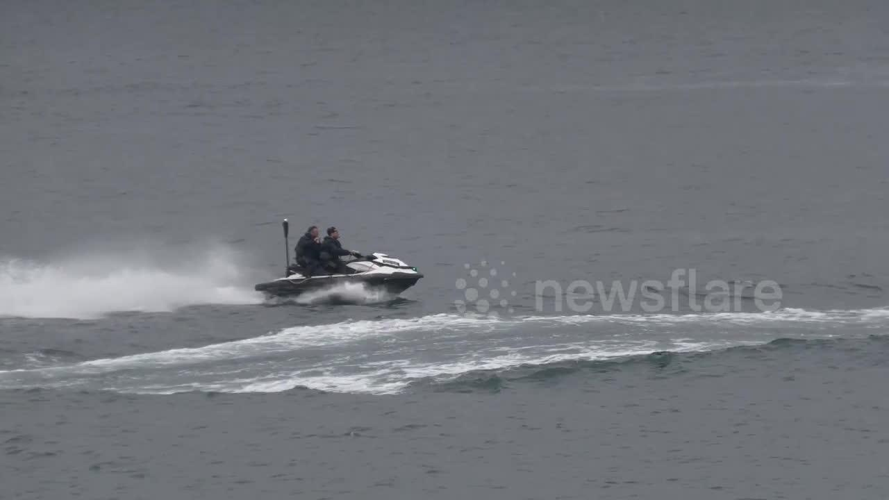 G7 police officers struggle to control a jet ski as they race past quiet Cornish town of St Ives