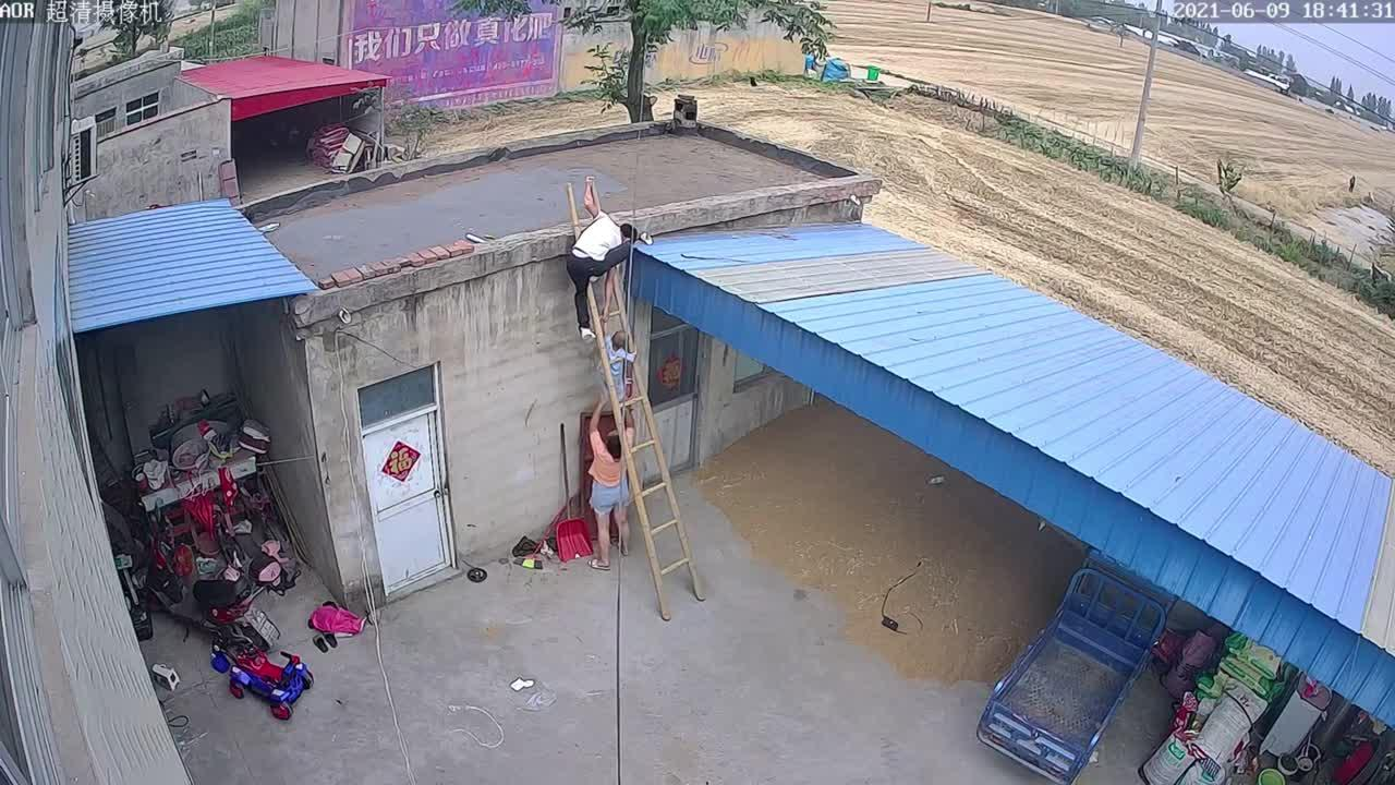 Chinese mother catches 2-year-old son after he followed father up ladder