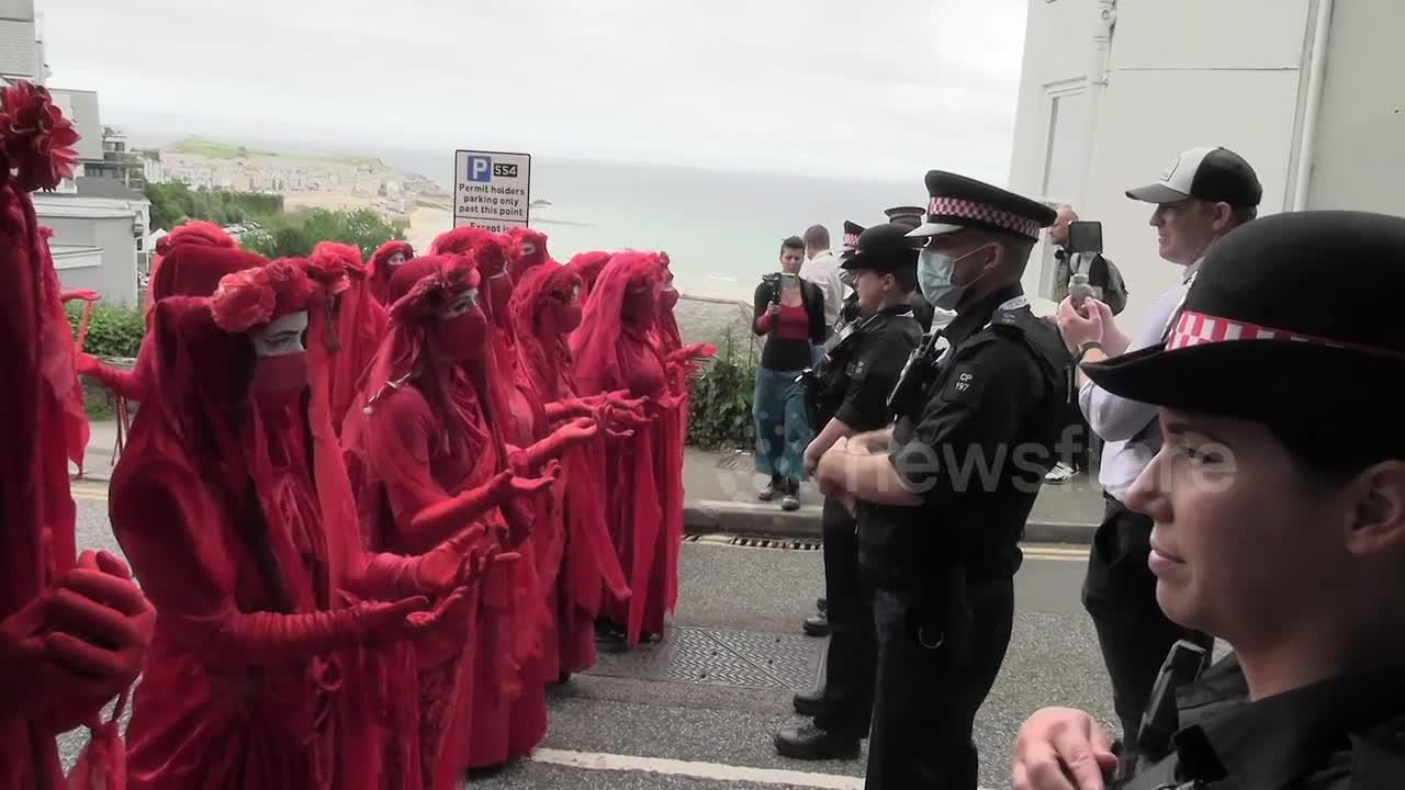 Red-robed protesters and pink boat seen at Extinction Rebellion's G-7 summit demonstration